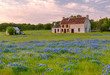An old rustic house sits nestled in a field of bluebonnets in Marble Falls, Texas