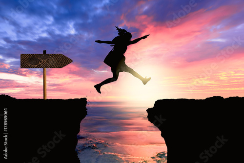 courageous and motivated woman jumps the crevasse
