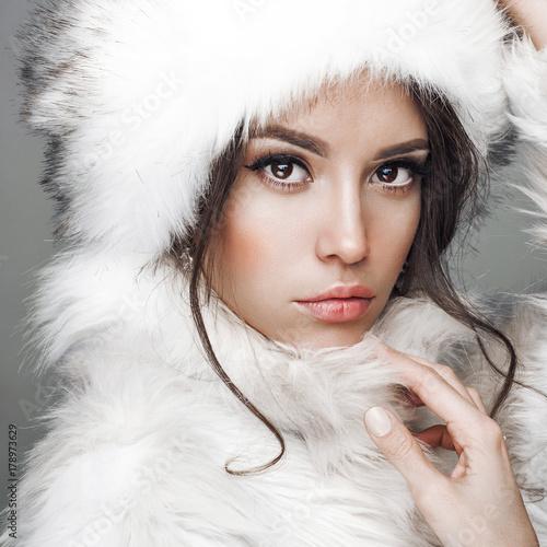 Beautiful woman in white fur coat and fur hat