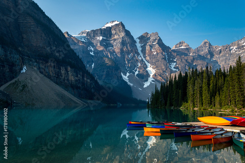 Fotobehang Canada A row of canoes sitting in the evening sun, ready to be taken on the water. Louise lake in Banff national park, Alberta, Canada