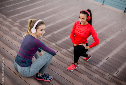 Two young women exercise outside