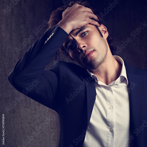 c5421098 Charismatic tired handsome business man in blue fashion suit and white  style shirt looking on dark