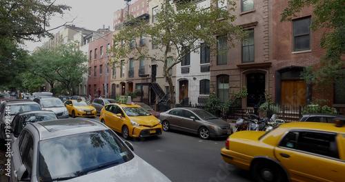 Papiers peints New York TAXI Wide view exterior shot of a typical generic New York City block with apartment buildings yellow taxi cab traffic and parked cars lining side of street.