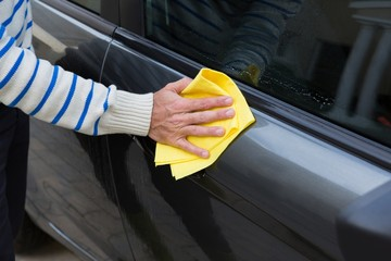Auto service staff cleaning a car with duster