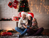 Adorable young couple sitting on a carpet with Santa hats hugged while looking on a tablet for Chrismas holidays. - 179012232