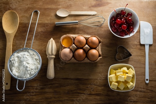 Aluminium Kersen Eggs, butter cubes, cherries, sieve and whisk on a wooden table