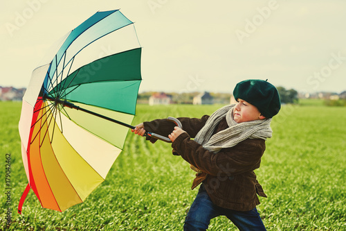 Juliste The child, standing under a colored umbrella on the green meadow