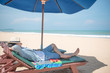 Quadro young man lying on wooden beach bench under blue umbrella and close his face by hat, beautiful tropical beach island and blue sky, vacation time and summer holiday concepts, digital nomad lifestyle