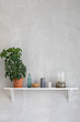 Small shelf with flowerpot and simple decor on gray wall.  - 179047614