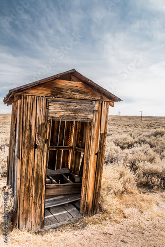 Old wooden outhouse in a desert Poster