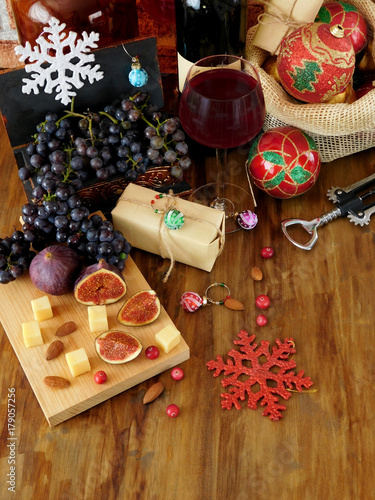 Foto op Aluminium Milkshake Cheese and figs on a wooden board, red wine in a glass, grape and Christmas attributes around. Christmas table laying