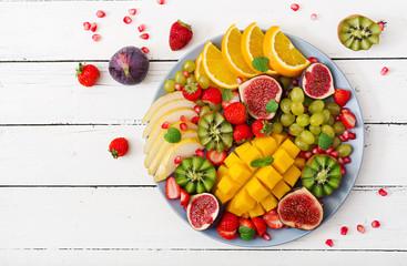 Platter fruits and berries. Mango, kiwi, fig, strawberry, grapes, pear and orange. Vegan cuisine. Dietary menu. Flat lay. Top view © timolina