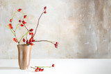 Rosehip branches in a stoneware vase on a white table in front of a vintage wall, natural beautiful autumn decoration with copy space - 179061680