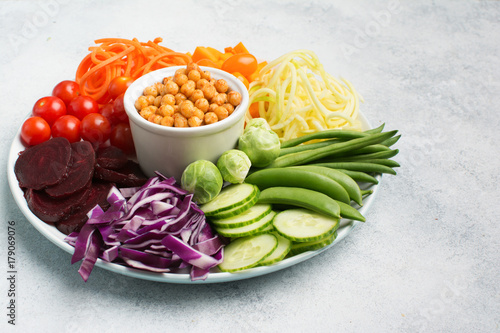 Foto op Canvas Boeddha Vegan eating concept, healthy salad bowl, colourful vegetables, carrot, courgette, cabbage, chickpeas, cucumber and tomatoes, on wooden board on white table, copy space, top view, selective focus