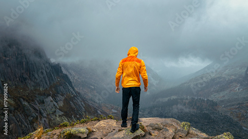 Foto op Canvas Boeddha a man stands on the precipice of the mountain in the fog
