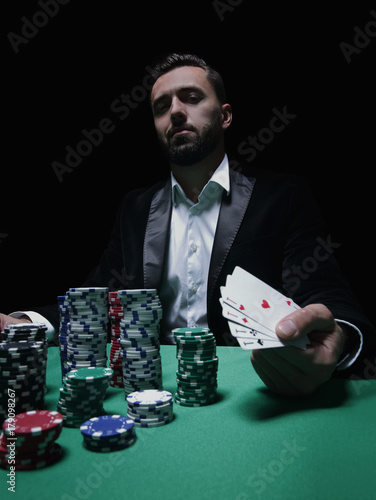 Happy poker player winning and holding a pair of aces плакат