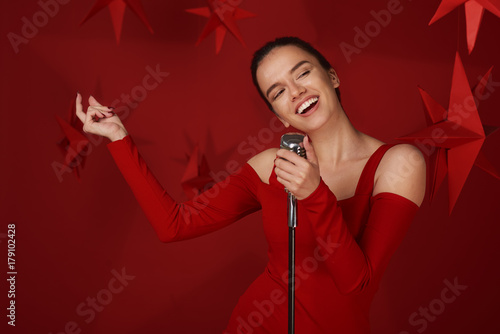 Fototapeta Girl singing and holding microphone. Red background and stars behind