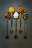 Bright spices in vintage spoons - saffron, salt, oregano, rosemary, red chili pepper on gray concrete background. Dark food photo.