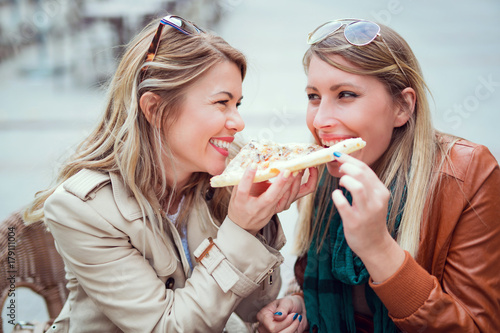 Papiers peints Pizzeria Portrait of two young women eating pizza outdoors,having fun together.