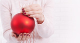 Christmas concept with hands and red, golden balls - christmas tree toy. Christmas baubles in female hands. - 179114829