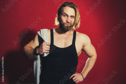 pumped-up man with a beard on a red background Poster