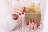 Present. Gift box. Woman holding small gift box with ribbon. - 179119026