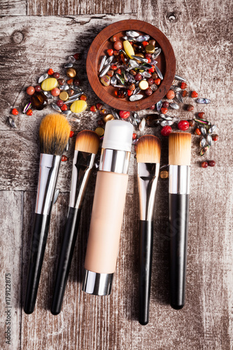 Poster Cosmetics products and brushes in conceptual image over wooden background