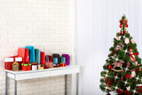 Christmas tree with present boxes over white brick wall - 179125464