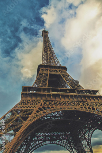 Foto op Canvas Eiffeltoren Eiffel tower view from the below angle with blue and cloudy sky, vintage filter applied