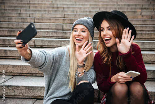 Portrait of two smiling happy girls taking a selfie