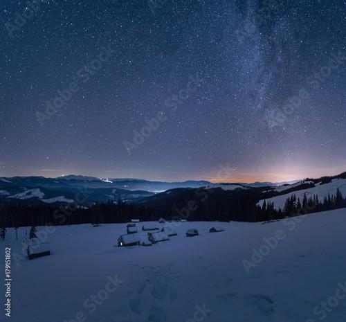 Papiers peints Bleu nuit Winter landscape of a mountain range at night. Stars over the mountain range. Snow covers slopes of a mountains.