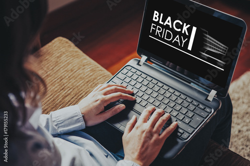 Black Friday advertisement in a laptop screen while woman uses it to buy by internet at home.