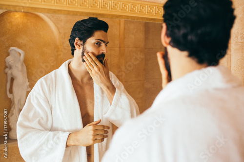 Young handsome bearded man looking in bathroom mirror a doing skincare