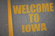 asphalt road with text welcome to iowa near yellow line.
