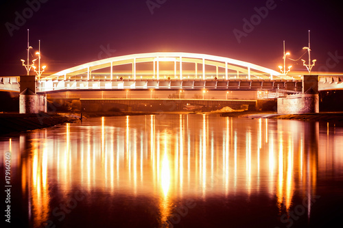 Night view to a bridge over river Warta in Poznan, Beautiful lights and reflections in calm water. Greater Poland.