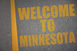 asphalt road with text welcome to minnesota near yellow line.