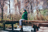 Boy sits omn wooden bridge over river in mountain autumn forest