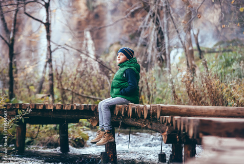 Boy sits omn wooden bridge over river in mountain autumn forest - 179164663
