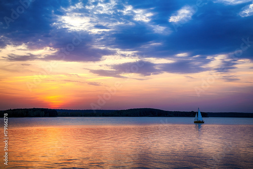 Foto op Canvas Zee zonsondergang Sailboat sunset fantasy sailing along its journey.