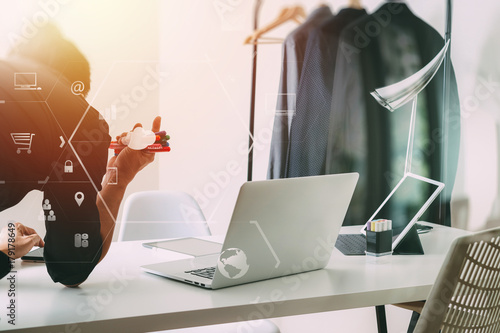 Fashion designer working with mobile phone and using laptop with digital tablet Poster