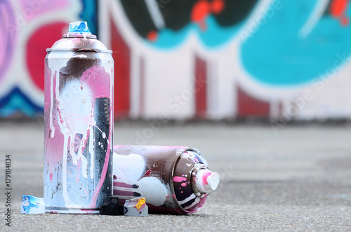 Several used spray cans with pink and white paint and caps for spraying paint under pressure is lies on the asphalt near the painted wall in colored graffiti drawings - 179184834