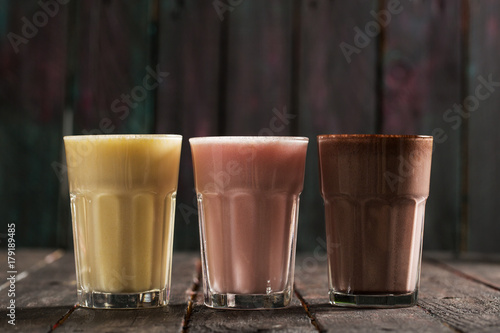 Foto op Aluminium Milkshake Delicious Milkshakes on Wooden Background
