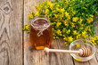Honey in transparent glass jar and fresh St. John's wort flowers on rustic background