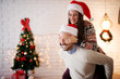 Close up of attractive playful love couple with Santa hats and sweaters having a piggyback ride for Christmas holidays in the living room.