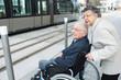 elderly lady pushing husband in wheelchair towards tram - 179199048