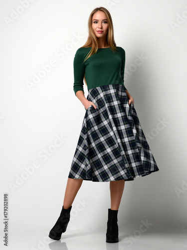 Plakat Young beautiful woman posing in new fashion plaid skirt and green blouse full bo