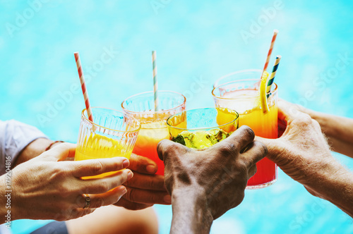 Poster Closeup of diverse hands clinking drinks together