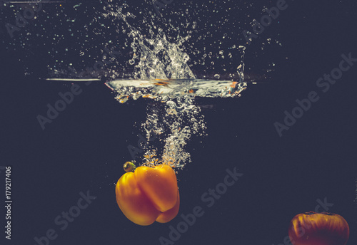 Green Yellow Red bell peppers drop into the water with splash. - 179217406