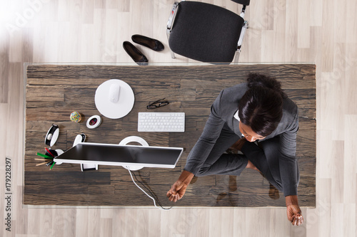 Woman Meditating In Office Poster