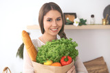 Young happy woman holding paper bag full of vegetables and fruits while smiling. Girl have made shopping and ready for cooking  in kitchen